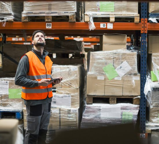 A man in a high-visibility jacket checking stock in a warehouse - Boyd Insurance